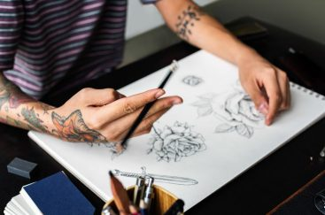 Closeup of tattooed hand with drawing artwork
